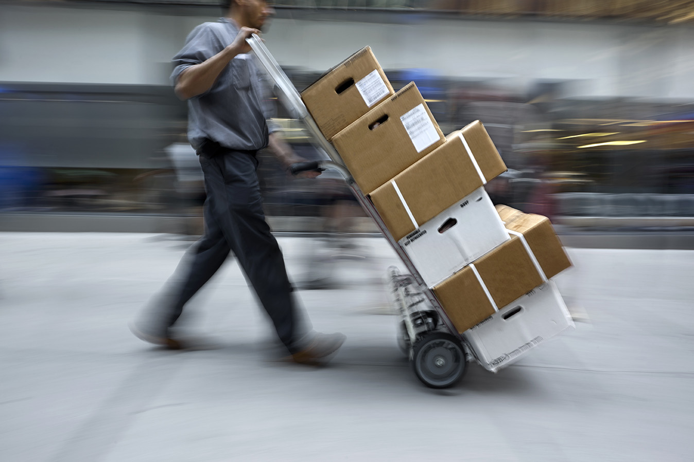 Delivery man with hand cart delivering boxes